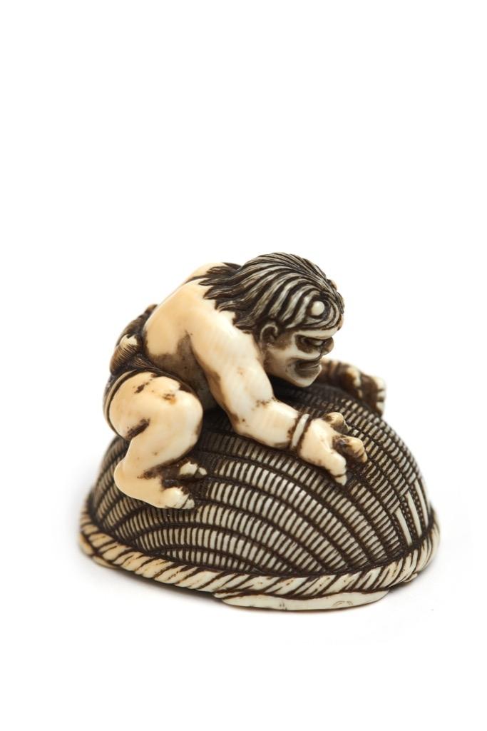 51- Japon XIX°. Netsuke en ivoire figurant un oni ayant enfermé Shoki sous un grand panier. Signé Okatori. Adjugé 2200€