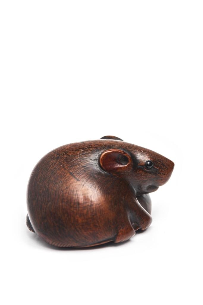 55- Japon, fin Epoque EDO. Netsuke en bois figurant un rat tenant un haricot sous ses pattes. Signé Motokazu. Adjugé 1500€