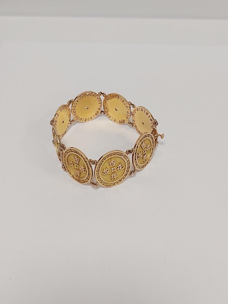 17-1 Bracelet en or jaune orné de motifs articulés à inscriptions chinoises. Poids 43,2g. Adjugé 1240€