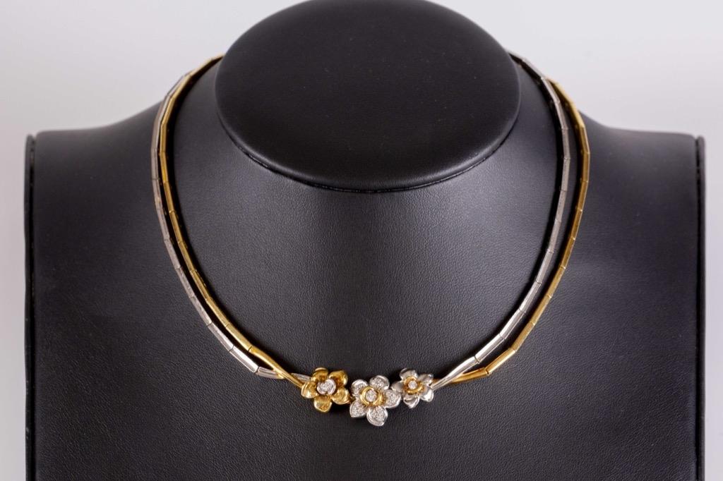 37 Collier rigide deux ors 18K 750° orné de diamants formant des fleurs. Poids brut 49g. Adjugé 1460€