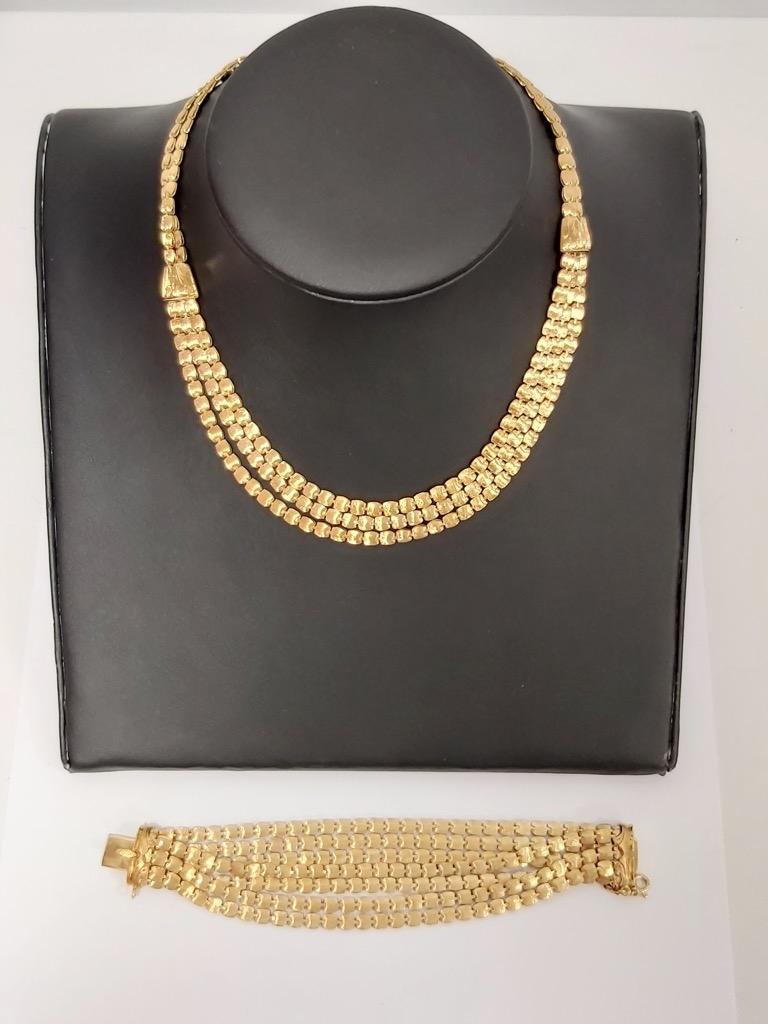 40-1 Parure en or jaune 18K 750° comprenant un collier noeud de cravate et un bracelet sept rangs. Poids total 107,5g. Adjugé 3350€