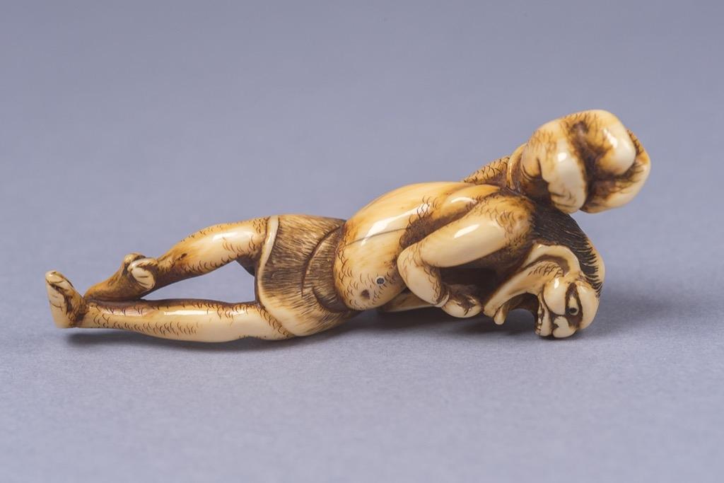 81 Japon, Epoque Edo (1603-1868). Netsuke en ivoire, Oni poilu rieur se tenant sur une jambe. Poids 15,6g. Adjugé 7600€
