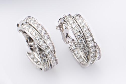 148 - CARTIER. Paire de clips d'oreilles en or blanc modèle Trinity serties de diamants pour un poids d'environ 4 carats. Adjugé 9600€