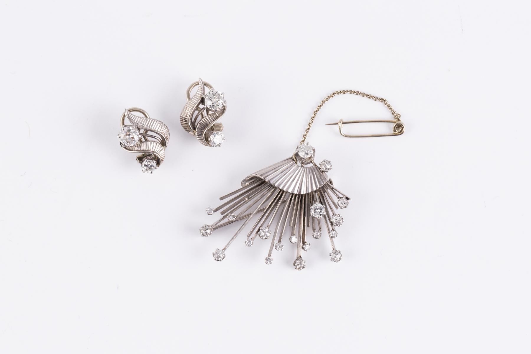 103- Une parure comprenant une broche en or gris sertie de petits brillants et une paire de clips d'oreilles. Adjugé 1300€
