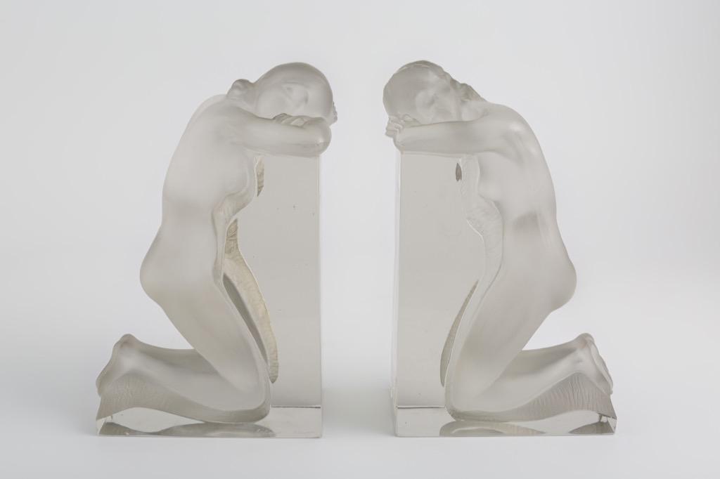 @1024-30 - LALIQUE France. Femmes nues agenouillées. Paire de serre-livres en verre moulé pressé blanc satiné signés. H22cm. Adjugé 650€