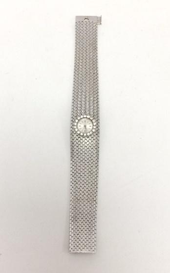 30-1 OMEGA Bracelet montre de dame en or gris la lunette sertie de diamants. Adjugé 1850€