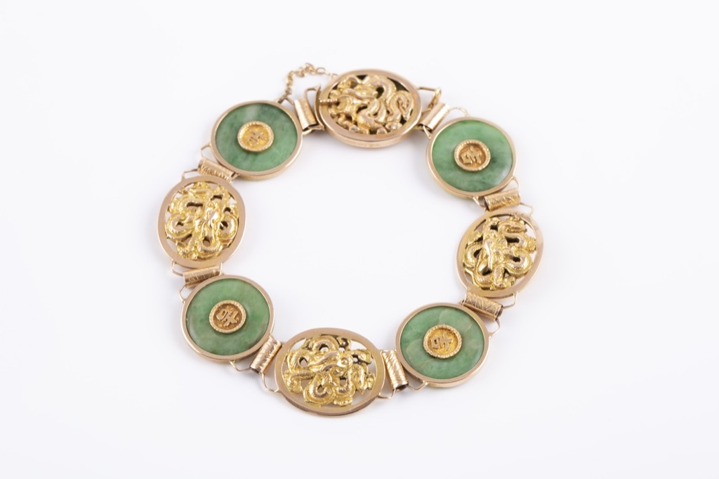 66 - Bracelet articulé en or étranger 14K à décvor de motifs en jade. Poids brut 21,78g. Adjugé 21,78g.