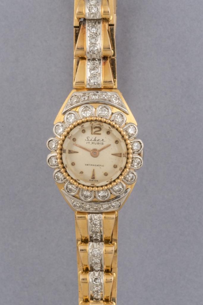 25 SIBER. Montre dame des années 50 en or, la lunette sertie de diamants. Poids brut 41g. Adjugé 1250€ 2